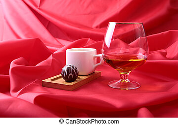 White cup of coffee and cognac in a glasses, pralines on red background.