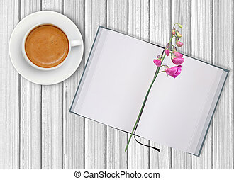 White cup of coffee and opened blank notebook with flower on wooden background