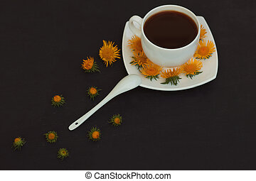 White cup of coffee on a dark background. Ornament from yellow flowers. Vintage tones.