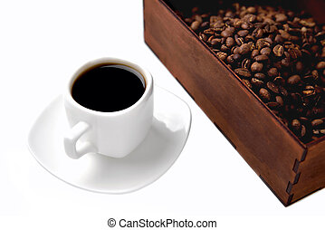 white cup of coffee on a white saucer, natural wooden box with coffee beans on a white background, angle view from above top