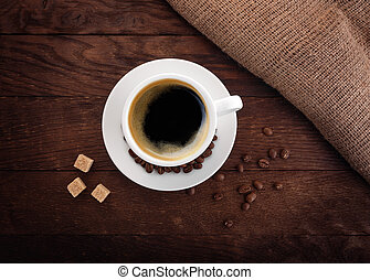 white cup of coffee on a wooden board grain burlap