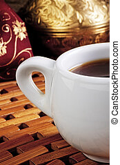White cup of coffee on a wooden stand