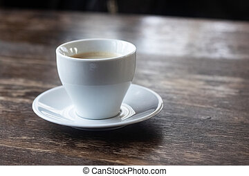 White cup of coffee on a wooden table