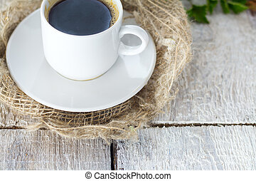 White cup of coffee on wooden background.