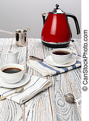 White cup of coffee on wooden kitchen table