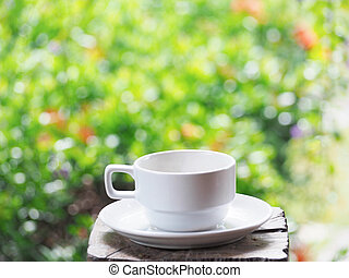 white cup of coffee over green floral abstract blur background.