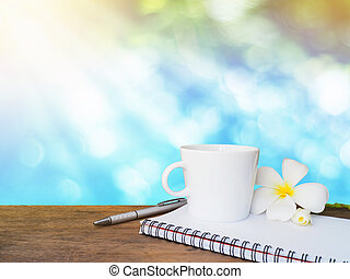 White cup of coffee, pen and notepad on wooden table
