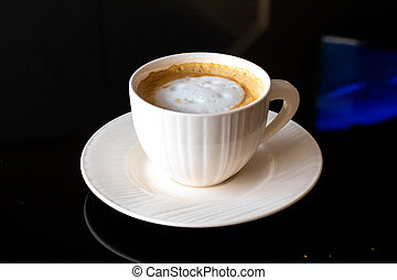 White cup of coffee, saucer on a black background.