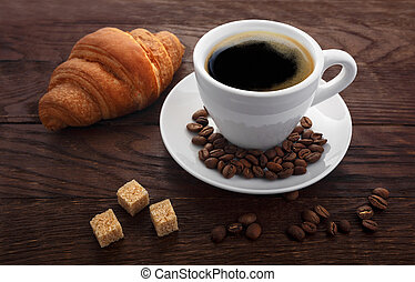 cup of coffee sugar croissant on a wooden background