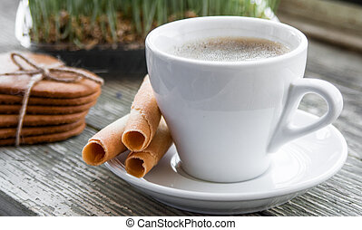 White cup of coffee with biscuits.