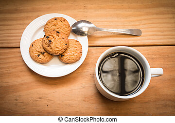 White cup of coffee with chocolate chips cookies