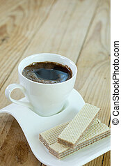 White cup of coffee with chocolate wafers over rustic wooden bac