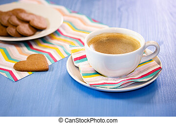 White cup of coffee with cookies on a blue table. Morning black hot coffee with homemade sweet pastries, heart-shaped gingerbread cookies