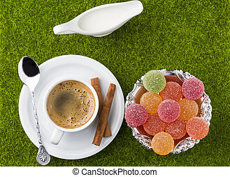 White cup of coffee with dessert on a green grass