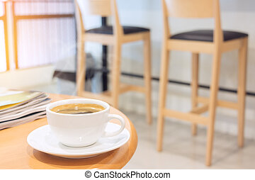White cup of coffee with magazine on wood table.