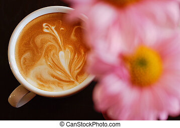 White cup of coffee with pink flower on black