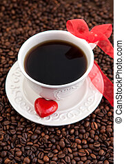 White cup of coffee with red heart on coffee beans
