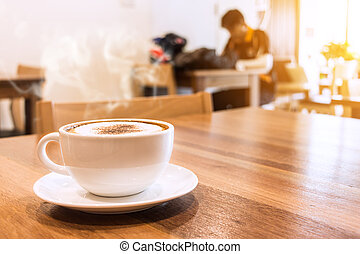 White cup of coffee with smoke on table in cafe.