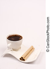 White cup of coffee with wafer chocolate cream rolls
