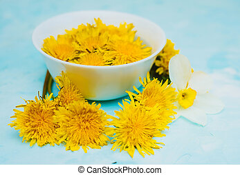 White cup of herbal tea over blue textured background decorated with yellow dandelions flowers and green leaves. 5 o'clock concept.