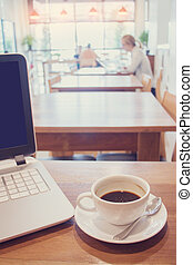 White cup of hot coffee with laptop on wooden table in cafe.
