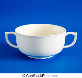 White cup of soup on blue background