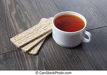 white cup of tea with cookies on a wooden table
