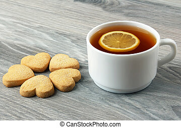 white Cup of tea with cookies on the table