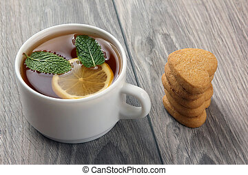 white cup of tea with lemon and cookies on a wooden table