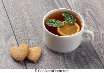 white cup of tea with lemon, mint and cookies on a wooden table