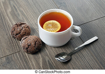 white cup of tea with lemon, teaspoon and cookies on a wooden table