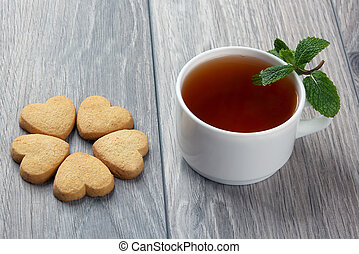 white cup of tea with mint and cookies on a wooden table