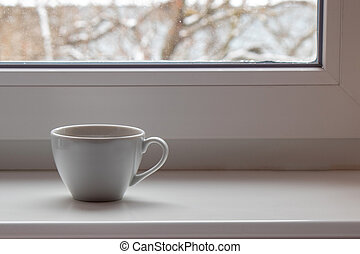 White cup on a white windowsill against the background of a snowy window