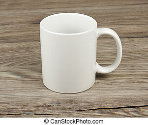 White cup on a wooden background.