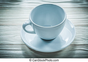 White cup saucer on wooden board
