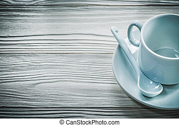 White cup saucer teaspoon on wooden board