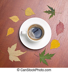 White cup with black coffee and autumn leaves