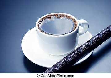 white cup with black coffee and chocolate on the saucer