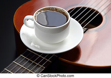 white cup with black coffee lying on the acoustic guitar