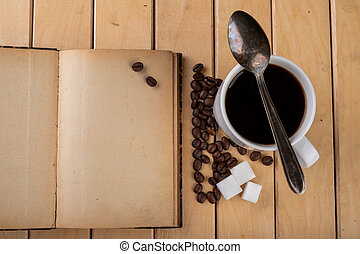 White cup with black coffee on a wooden table. Grains of coffee on an old book.