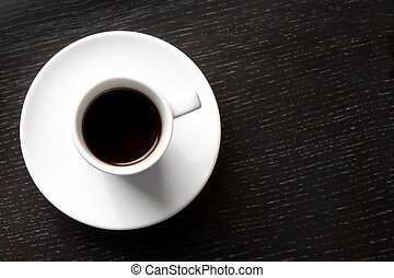 top of view of a white cup with coffee with space for text over wood black table