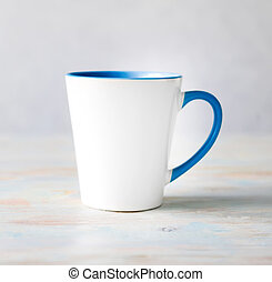 white cup with blue handle and inner surface