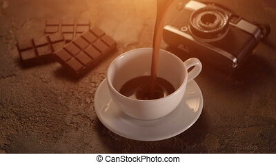 White cup with chocolate bar and retro camera on texture table