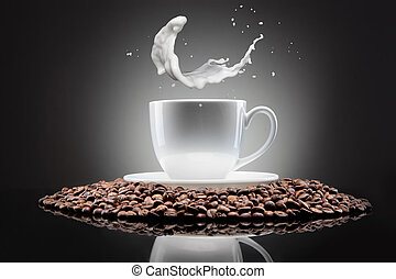 white cup with coffee beans and milk splash on black