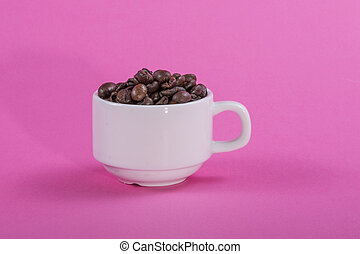 White cup with coffee beans on a pink background