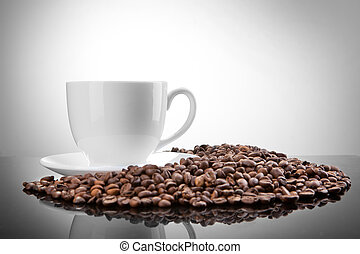 white cup with coffee beans on white