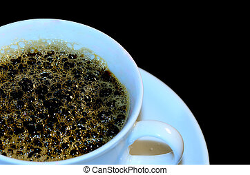 white cup with coffee foam and black background