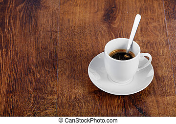 white cup with coffee on a wooden table