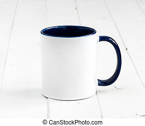 white cup with dark blue inside on a table