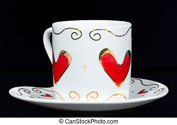 White cup with hearts isolated on black background.